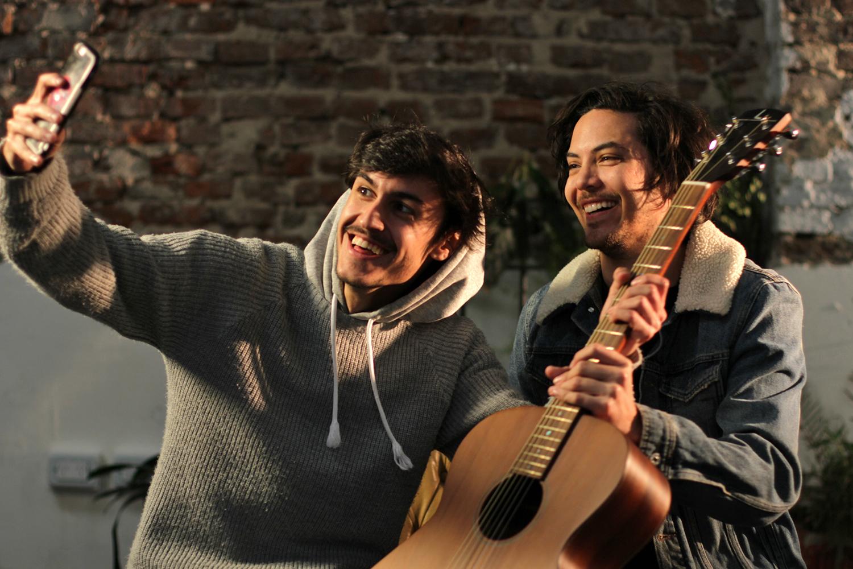 Dos chicos con guitarra sacando selfie