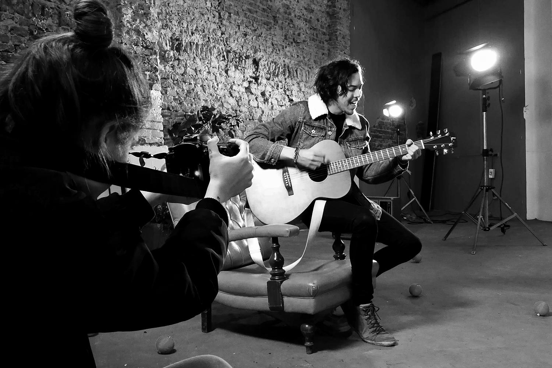 Mujer fotografiando hombre tocando la guitarra