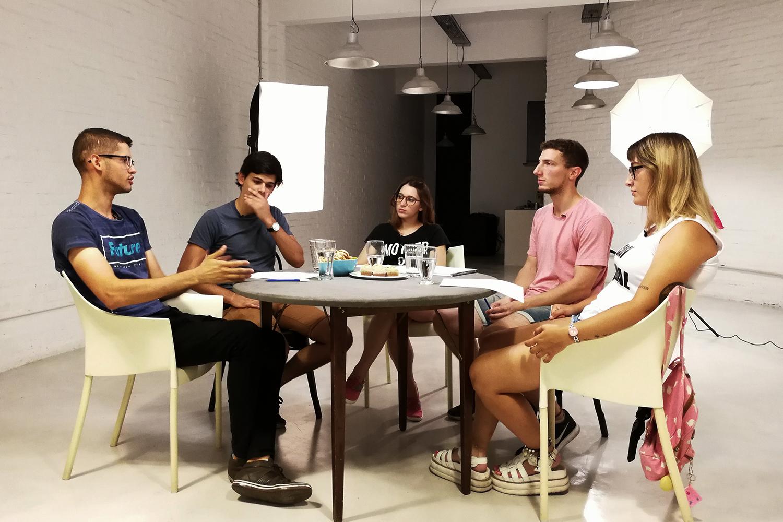 Cinco jóvenes reunidos alrededor de una mesa
