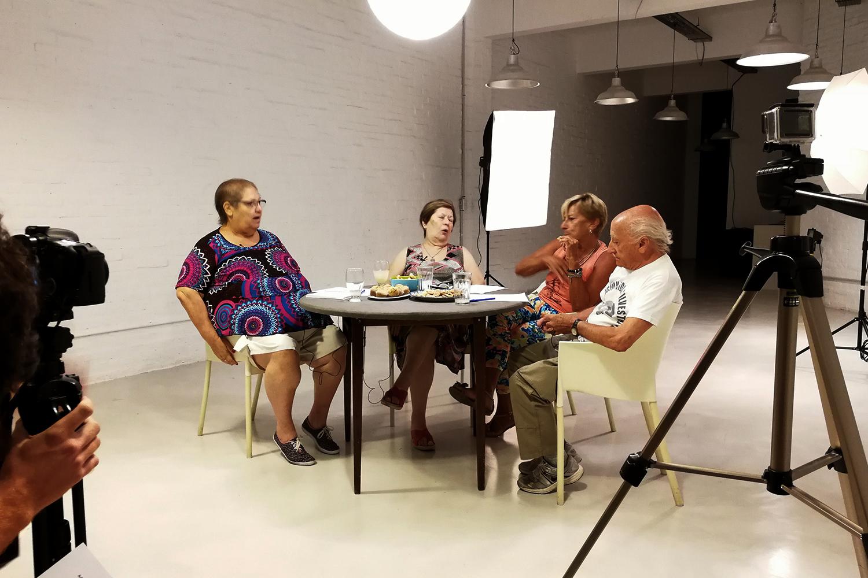 Cuatro personas mayores reunidas alrededor de una mesa